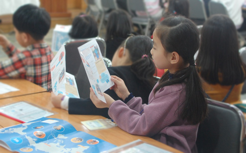 Kind liest im VIELFALT Heft/ A Child reading the DIVERSITY booklet (Photo: Heekyung Jeong/EMS)