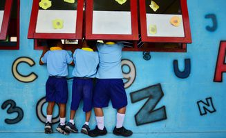 Kinder spicken in die Fenster einer Grundschule hinein. / Children peek through a primary school window. (Photo: UNESCO/ Alland Dharmawan)